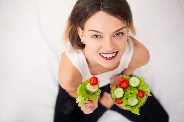 Young woman eating healthy salad after workout