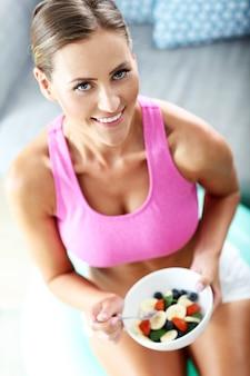 Молодая женщина ест здоровый салат после тренировки