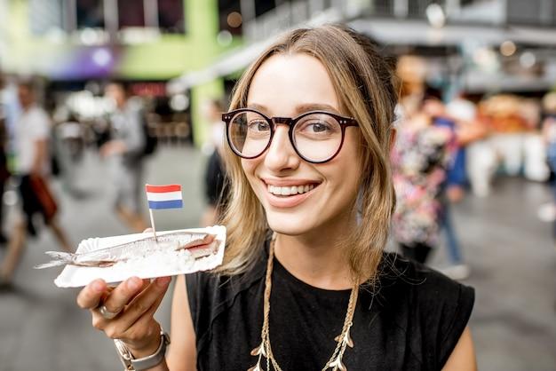 ロッテルダム市場で玉ねぎと伝統的なオランダのおやつとニシンを食べる若い女性