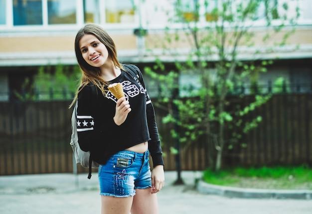 Молодая женщина ест мороженое в солнечный день на открытом воздухе возле большого дома