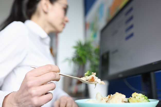 Young woman eating lunch do not look away from computer monitor