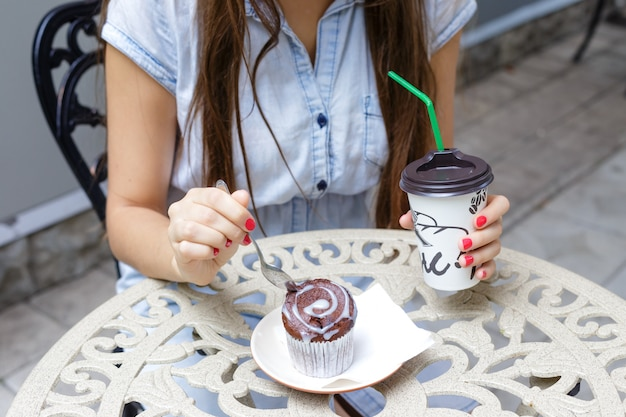 Young woman eating muffin and drink coffee in outdoors cafe, close up
