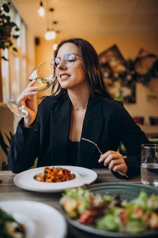 Giovane donna che mangia pasta in un caffè