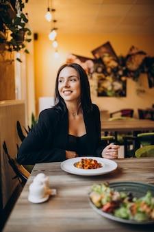 カフェでパスタを食べる若い女性