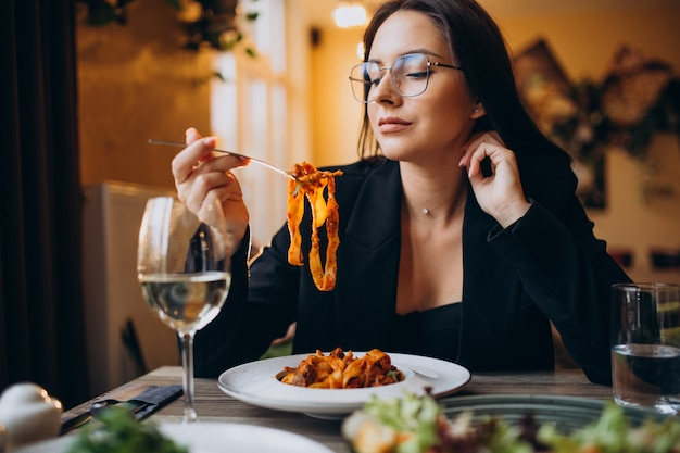 Молодая женщина ест макароны в кафе