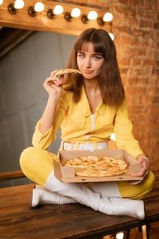 黄色いコンビネに座ってピザを食べる若い女性