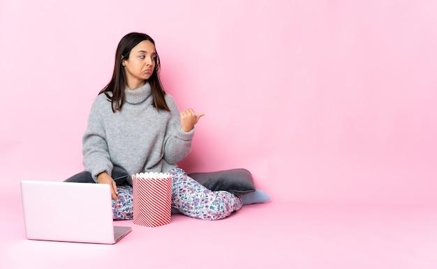 불행하고 측면을 가리키는 노트북에서 영화를 보면서 팝콘을 먹는 젊은 여자