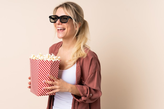 Young woman eating popcorns over isolated background
