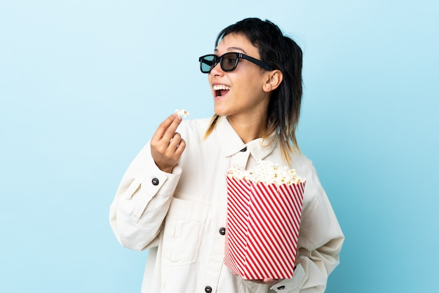 Young woman eating popcorns over isolated wall