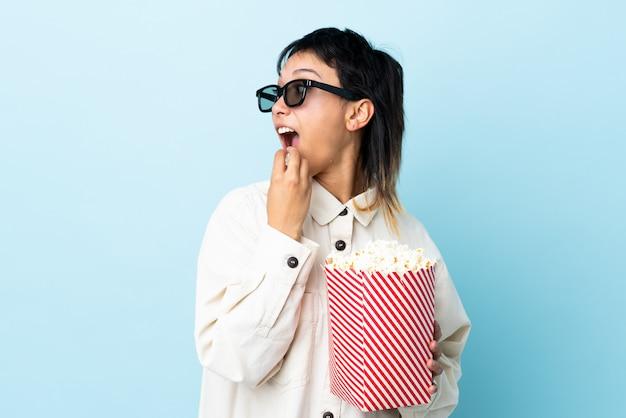 Молодая женщина ест попкорн на изолированном фоне