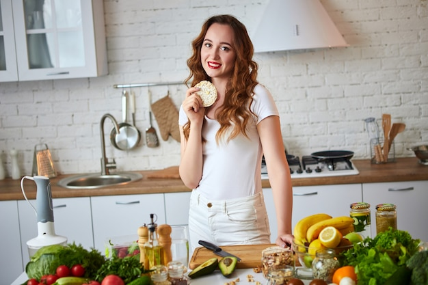 Young woman eating rye cracker crisp bread in the kitchen. healthy lifestyle. health, beauty, diet concept.