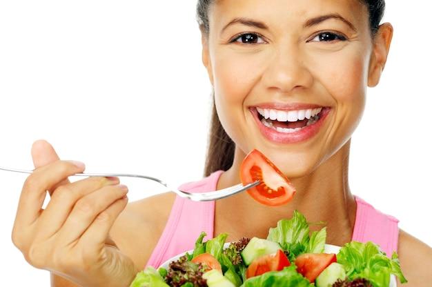 サラダを食べて、混合サラダを保持している若い女性