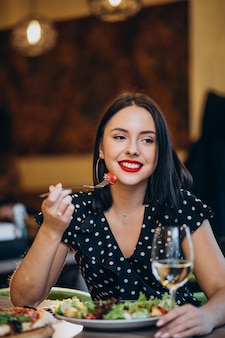 Молодая женщина ест салат в кафе