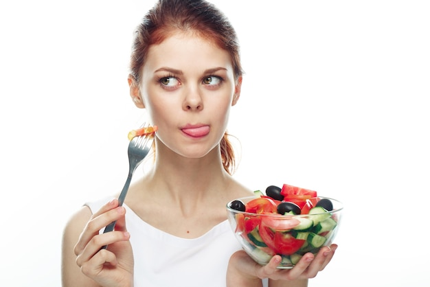 Young woman eating salad isolated
