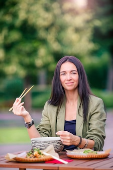 Young woman eating take away noodles on the street