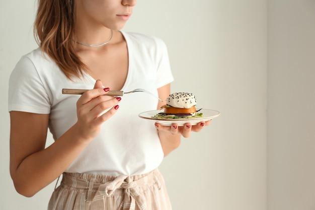 Молодая женщина ест вкусный салат на светлой поверхности
