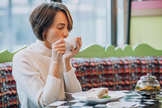Young woman eating tiramisu with tea at a cafe