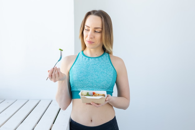 Young woman eating vegetable and meat after workout