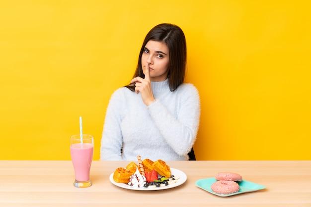 沈黙のジェスチャーをしているテーブルでワッフルとミルクセーキを食べる若い女性