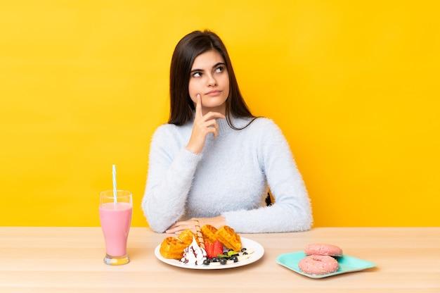 アイデアを考えて孤立した黄色の背景の上のテーブルでワッフルとミルクセーキを食べる若い女性