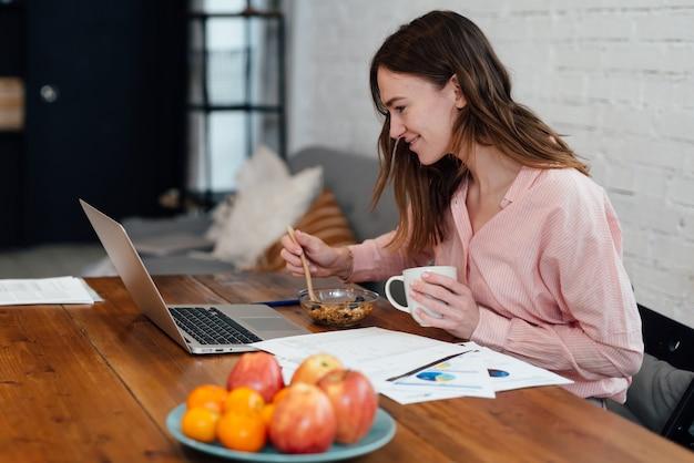 Молодая женщина ест завтрак, сидя перед своим ноутбуком.