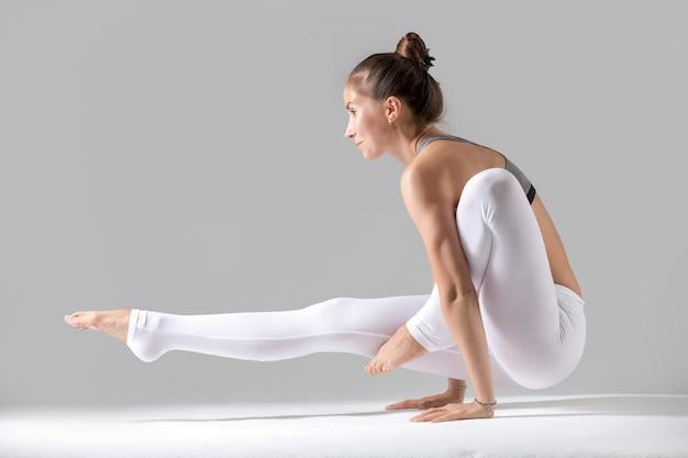 Young woman in eka hasta bhujasana pose, grey studio background
