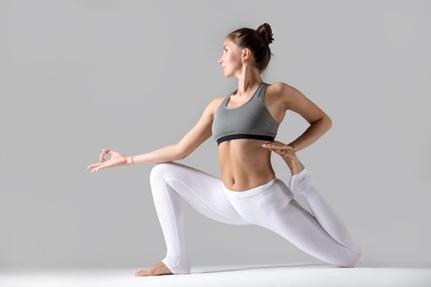 Young woman in eka pada rajakapotasana pose, grey studio background