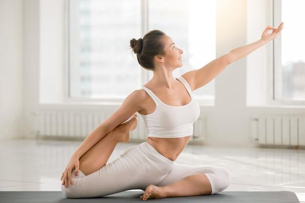 Young woman in eka pada rajakapotasana pose, white color backgro