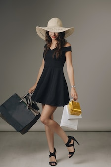 Young woman in elegant black dress and summer hat
