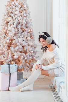 Young woman in an elegant dress near the christmas tree