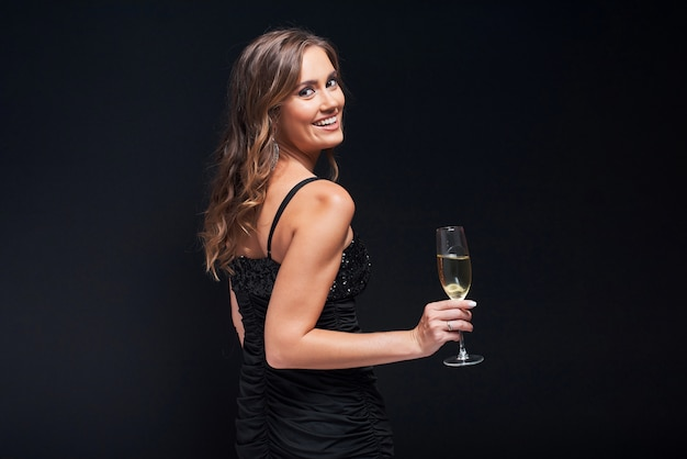 Young woman in elegant dress staying with glass of champagne against black