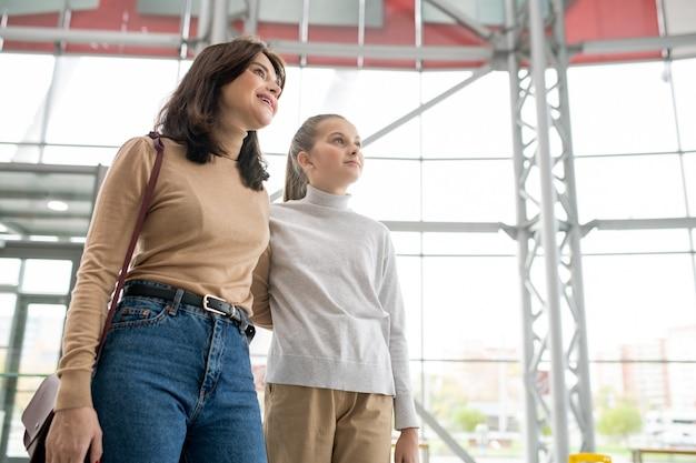 大規模な貿易センターでのショッピング中に両方の新しい部門を見ながら彼女の娘を抱きしめる若い女性