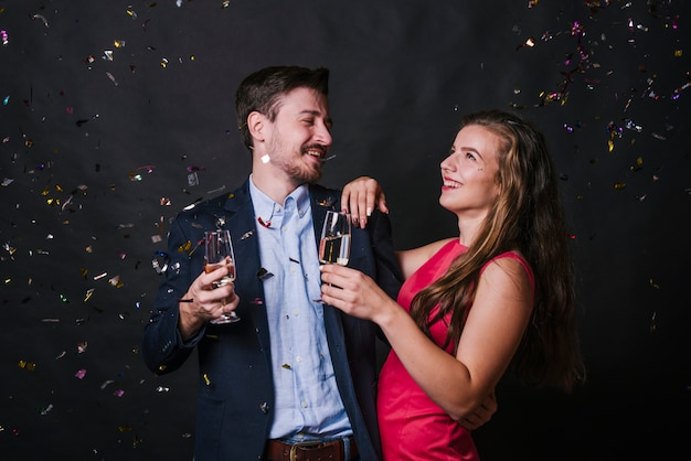 Young woman embracing man with glasses of drink between tossing confetti