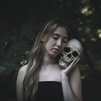 Young woman embracing skull in woods