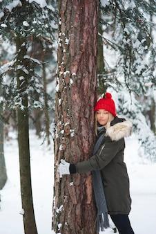 Молодая женщина, обнимая дерево в зимнем лесу