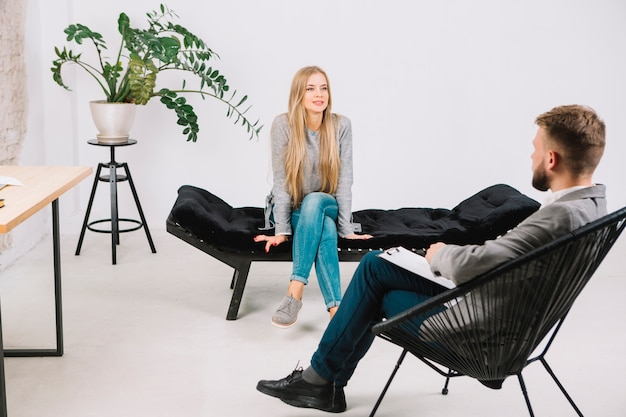 Young woman emotionally speaking and discussing with psychotherapist her problems