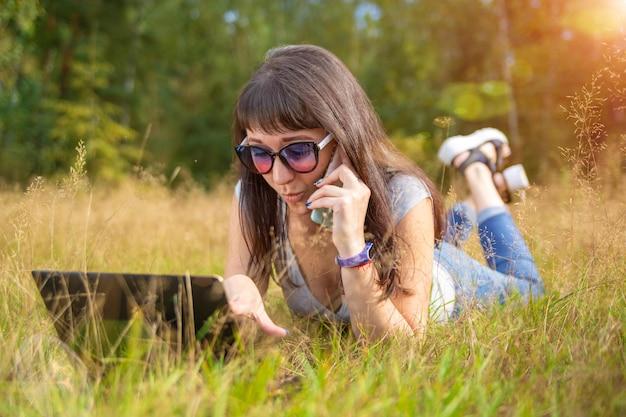 Молодая женщина эмоционально разговаривает по телефону и смотрит в ноутбук. женщина-фрилансер работает в