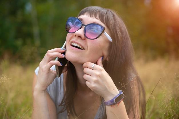 Молодая женщина эмоционально разговаривает по телефону на лужайке в солнечный день. счастливые эмоции на лице.