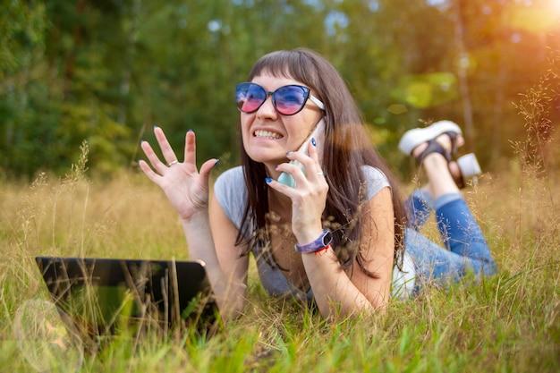 Молодая женщина эмоционально разговаривает по телефону перед ноутбуком.