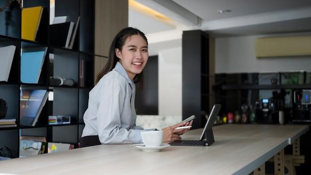 Сотрудник молодой женщины держа мобильный телефон и усмехаясь к камере.