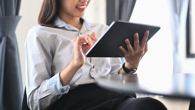 オフィスに座ってデジタルタブレットを使用している若い女性従業員。
