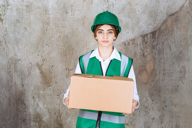 Young woman engineer in green vest and helmet holding paper box