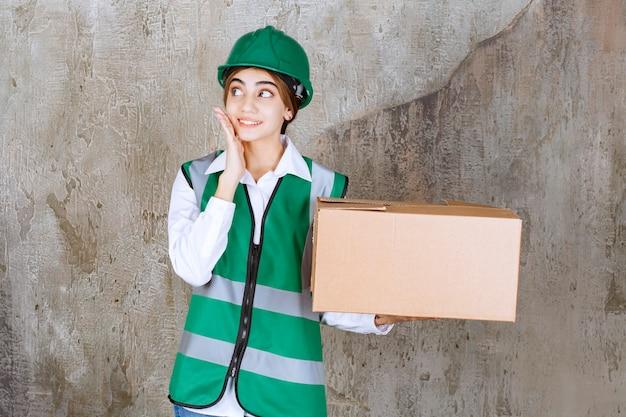 Молодая женщина-инженер в зеленом жилете и шлеме, держа бумажную коробку