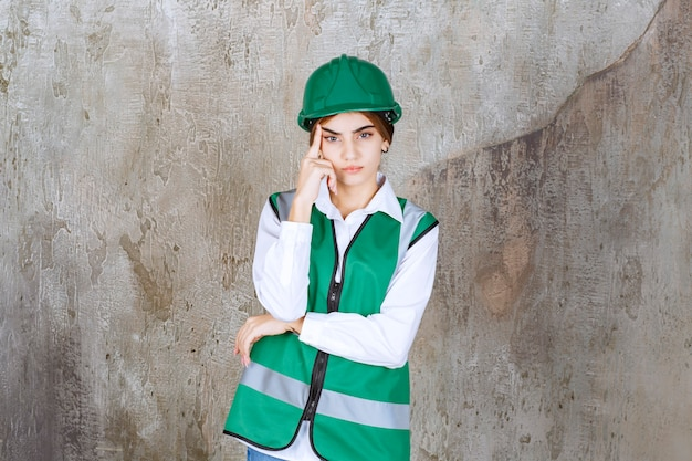 녹색 조끼와 헬멧 서서 포즈를 취하는 젊은 여성 엔지니어