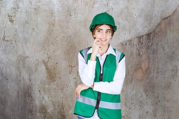 Молодая женщина-инженер в зеленом жилете и шлеме стоя и позирует