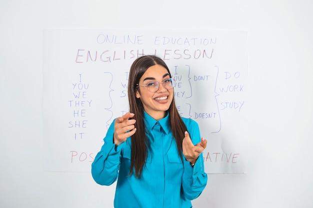 カメラにオンラインレッスンを与えるホワイトボードに立っている若い女性の英語教師。検疫封鎖中の自己隔離での自宅での教育。