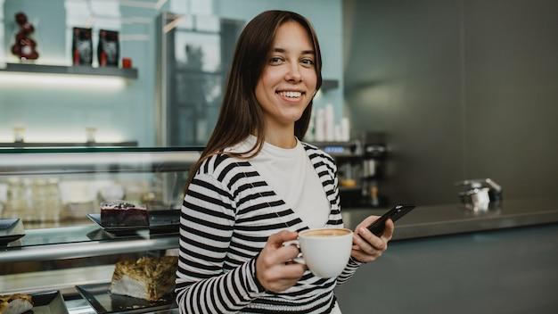 Молодая женщина, наслаждаясь чашкой кофе