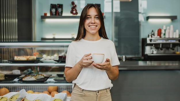 コーヒーカップを楽しんでいる若い女性