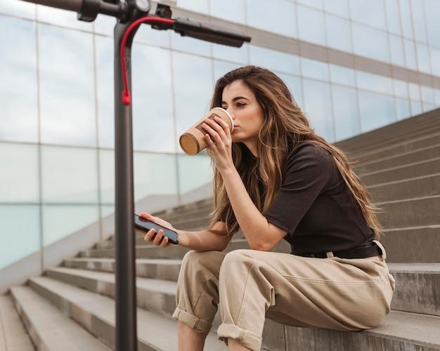 Молодая женщина, наслаждаясь кофе