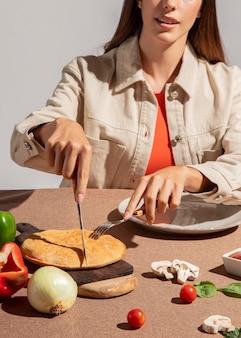 Молодая женщина, наслаждаясь вкусной пиццей кальцоне